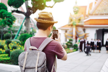 Young Asian traveling backpacker taking photos with smartphone in Wat Arun in Bangkok, Thailand