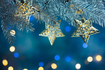 fir tree branch decorated with garlands on blue background with blurred christmas lights