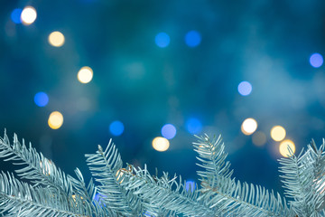silver christmas tree branch on blurred blue background with holiday lights