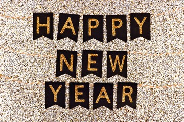Happy New Year banner with glittery text on black flags against a glittery gold background