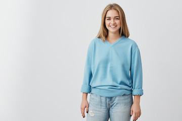 Cheerful beautiful woman with straight fair hair having dark charming eyes and engaging smile posing at studio against gray background. Pretty smiling girl wearing blue sweater and jeans.
