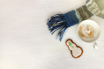 winter coffee break with mood/ white mug with cappuccino in blue scarf and ginger snowman on table top view
