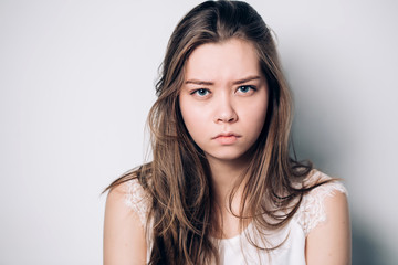 Close up isolated portrait of young annoyed angry woman. Young female in white T-shirt. Negative human emotions, face expressions.