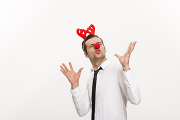 Christmas Concept - Handsome Business man wearing reindeer hairband making funny facial expression.