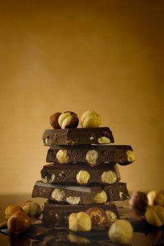 Dark chocolate with hazelnuts on golden background
