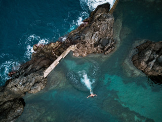 Aerial of an adult male swimming, jumping and playing in a natural swimming pool on Madeira, Portugal