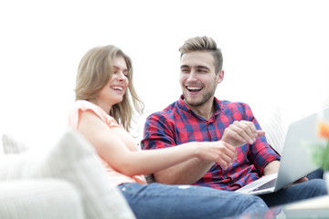 young man and his girlfriend cheering for their team while sitting on the couch