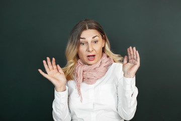 Portrait of emotional shocked senior woman with blonde loose hair looking in front of her with mouth wide opened, raising hands, feeling terrified and scared with spider or mouse. Fear and shock