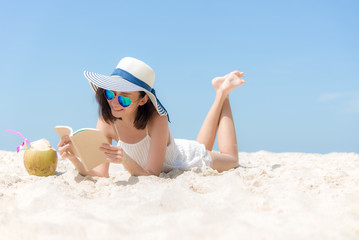 Lifestyle young asian woman relax and reading a book at the beautiful beach on holiday summer, blue sky background.  Summer Concept..