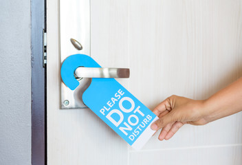 Woman hand holding signboard do not disturb hanging on the door.