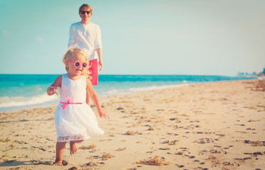 cute little girl with father play on beach