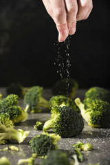 Chef is salting grilled broccoli pieces on the kitchen table. Healthcare concept.