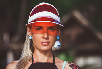 Portrait of a beautiful girl in a red visor closeup. Wearing Large turquoise earrings. Holiday in Thailand