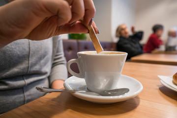 Junge Frau streut zucker in Kaffee mit unscharfem hintergrund