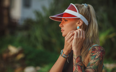 Portrait of a beautiful girl in a red visor closeup. Corrects large earrings. Holiday in Thailand