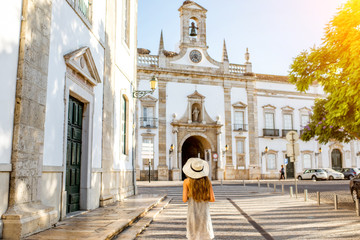 Young woman in hat in front of church, Faro, Portugal Fototapete
