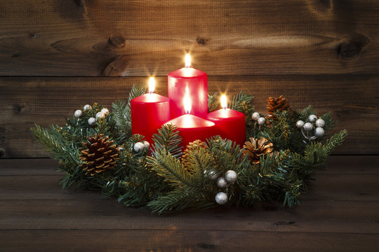 Fourth Advent - Decorated Advent wreath with four red burning candles on a wooden background