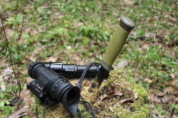 A green knife, a night vision device and a lantern on a stump covered with moss, against a background of green forest