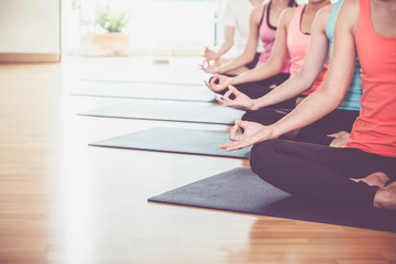 Close up hands of yoga group seated doing Hand Mudra and meditates in a training studio fitness room, Calm and relax concept,wellness and healthy lifestyle,leave space for adding text.
