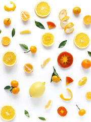 Creative flat layout of fruit, top view. Sliced orange, lemon, persimmon, tangerine, green leaves isolated on white background. Food wallpaper, composition pattern of fresh fruits.