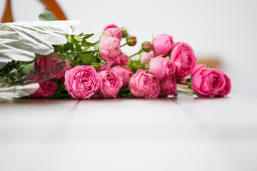 Photo of bouquet of pink peonies on white wooden table