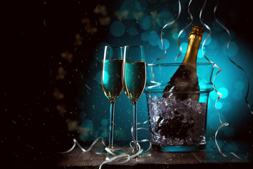 New Year's photo of two glasses, buckets of ice and bottle of wine on background with blue fire