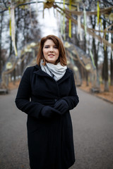 Photo of young woman in black coat and scarf