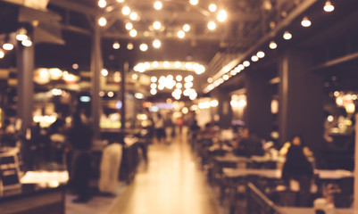 Blur of people in night cafe with lighting bokeh
