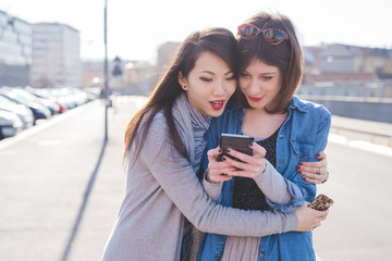 two young women friends using smart phone