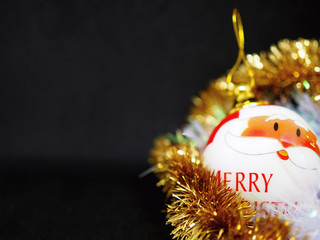 """Christmas ball with Santa Claus and the words """"merry Christmas"""" for the tree, on a black background, the ball is in the serpentine"""