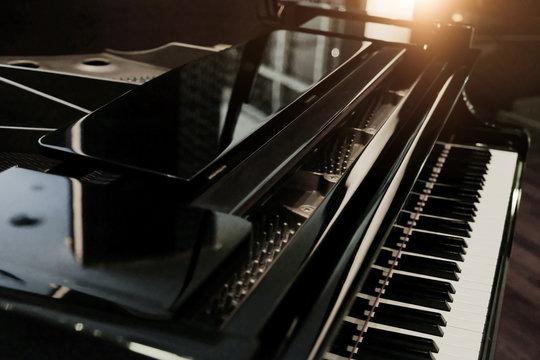 Black shiny grand piano with white keyboard in dark tone