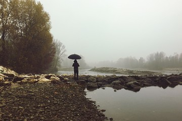 uomo con ombrello vicino al lago