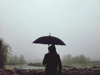 uomo con ombrello nella nebbia vicino al fiume