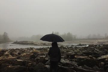 uomo nella nebbia con ombrello nella natura