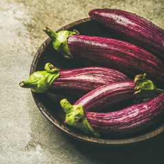 Fresh raw Fall harvest purple eggplants or aubergines in wooden bowl over grey concrete stone background, selective focus, square crop. Healthy Autumn vegan cooking ingredient