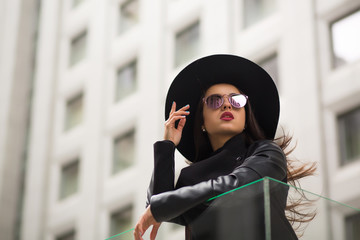 Fashion portrait of pretty woman in wide brimmed black hat and mirror sunglasses