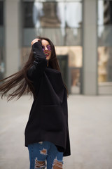 Happy brunette woman with hair blowing in the wind walking at the city mall