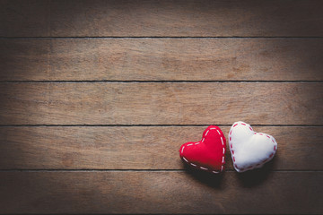 Two heart shape toys on wooden background