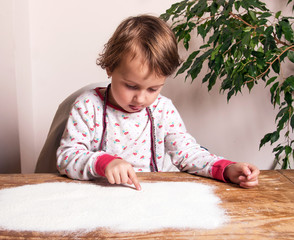 Beautiful little girl draws on a board with scattered flour (creativity, upbringing, relaxation, antistress - concept)
