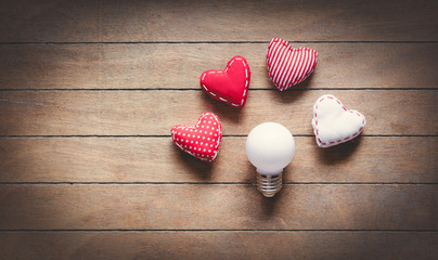 Heart shape toys and bulbs on wooden background