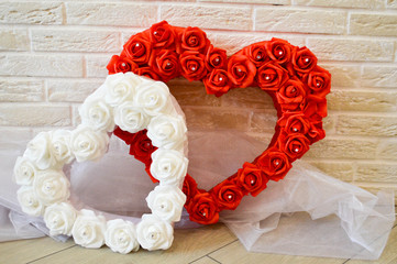 Two hearts. Red and white hearts with a pattern of roses with rhinestones against a brick wall.