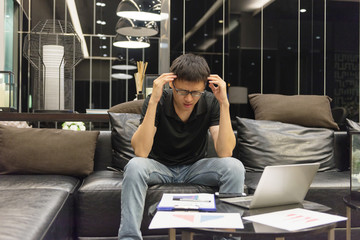 Stressed Asian businessman using a smartphone in living room at night