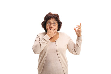 Surprised senior lady covering her mouth with her hand