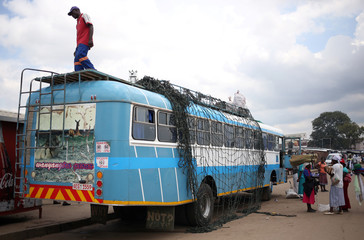 Women chat in front of a bus as a worker waits to load luggage at a bus terminus in Mbare township, outside Harare