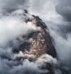 Wall Mural - Majestical scene with mountains in clouds in overcast evening in Nepal. Landscape with beautiful high rocks and dramatic cloudy sky at sunset. Nature background. Fairy scene. Amazing mountains