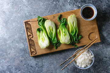 Stir fried bok choy or chinese cabbage with soy sauce and bowl of rice served on decorative wooden cutting board with chopsticks over gray texture background. Top view with space. Asian style dinner