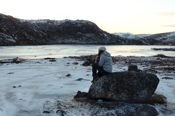 Woman traveler sitting on the large rock with beautiful landscape of frozen lake