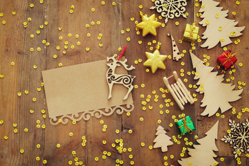 Top view image of christmas festive decorations next to empty note on old wooden background