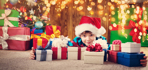 Boy lying on the floor with presents near christmas tree. Child in red hat at home in winter