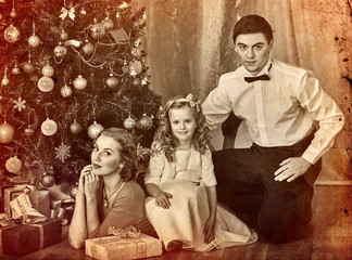 Christmas family photo with mother, father and girl in boxing day. Black and white Xmas vintage image with child by home interior.